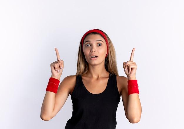 Giovane ragazza di forma fisica in abiti sportivi neri e fascia rossa che sembra sorpresa rivolta verso l'alto con le dita indice in piedi sul muro bianco