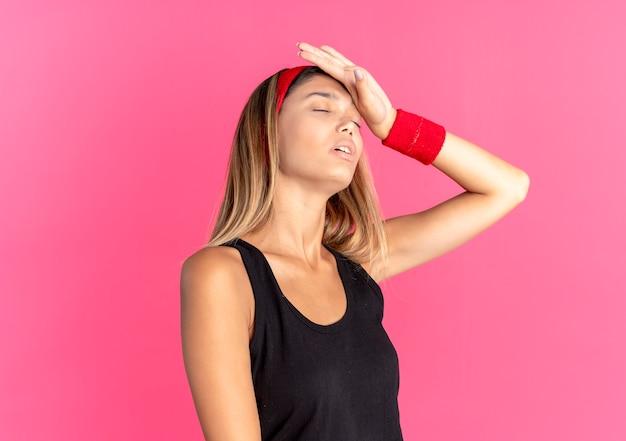 Giovane ragazza di forma fisica in abiti sportivi neri e fascia rossa che sembra stanca ed esausta sopra il rosa