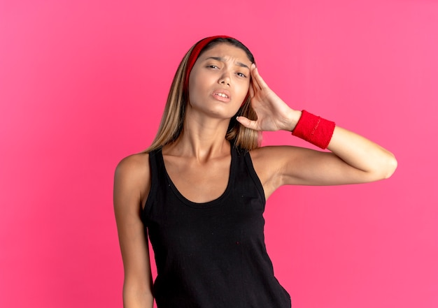 Giovane ragazza di forma fisica in abbigliamento sportivo nero e fascia rossa che sembra indisposto avendo mal di testa in piedi sul muro rosa