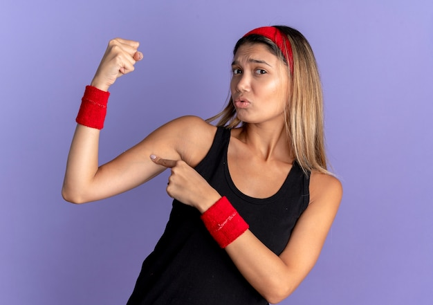 Young fitness girl in black sportswear and red headband raising fist showing biceps pointing with finger at it looking confused standing over blue wall