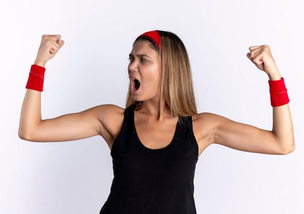 Giovane ragazza di forma fisica in abiti sportivi neri e fascia rossa che alza i pugni che grida con la faccia seria che grida in piedi sopra il muro bianco