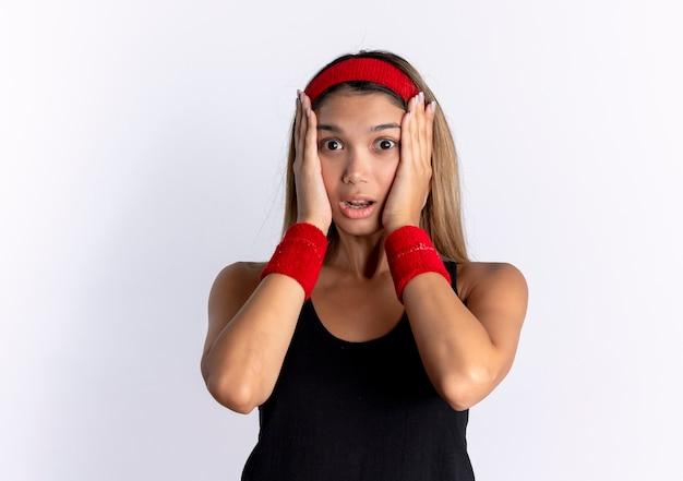 Giovane ragazza di forma fisica in abiti sportivi neri e fascia rossa sorpresa e stupita tenendo il viso con le mani in piedi sopra il muro bianco