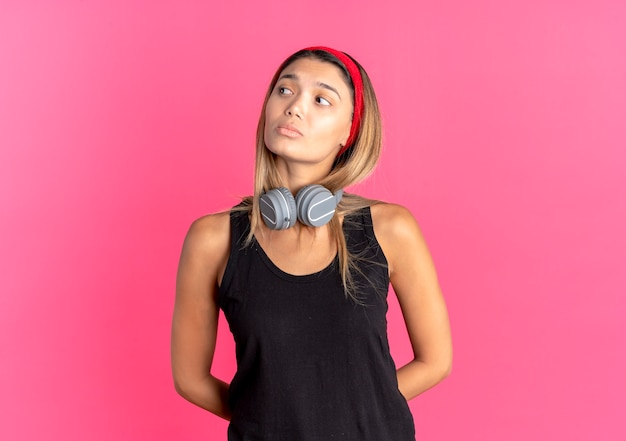 Young fitness girl in black sportswear and red headband with headphones looking aside confused with sad expression over pink