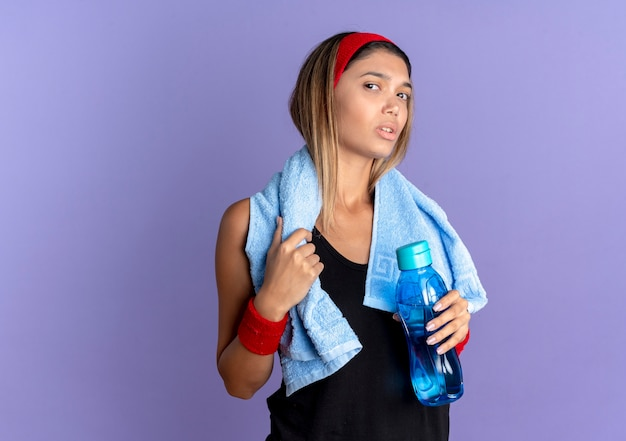 Young fitness girl in black sportswear and red headband with towel around neck  confused holding bottle of water standing over blue wall