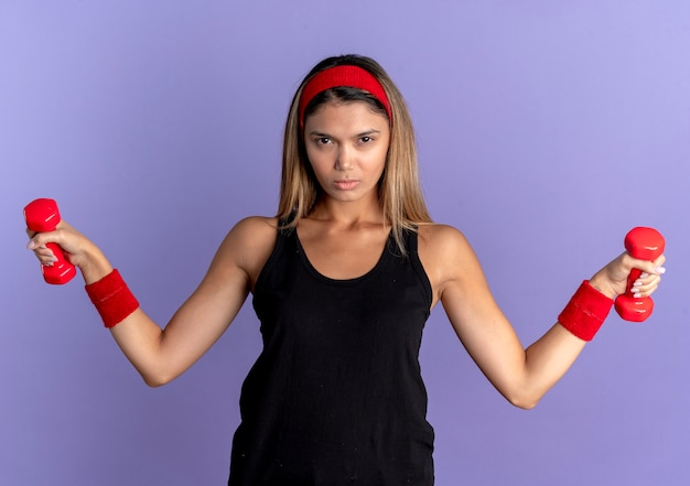 Giovane ragazza di forma fisica in abbigliamento sportivo nero e fascia rossa che risolve con il lookign dei manubri alla macchina fotografica con la faccia seria sopra l'azzurro