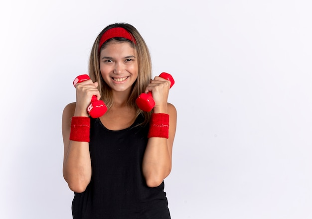 Giovane ragazza di forma fisica in abbigliamento sportivo nero e fascia rossa che risolve con il lookign dei manubri che sorride allegramente in piedi sopra il muro bianco