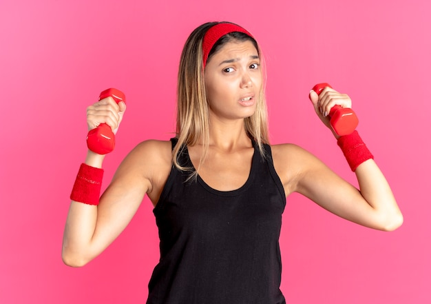 Young fitness girl in black sportswear and red headband working out with dumbbells looking confused standing over pink wall
