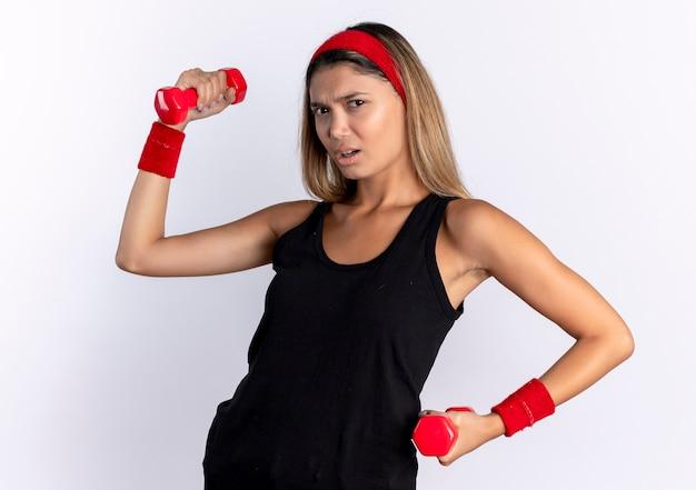Giovane ragazza di forma fisica in abbigliamento sportivo nero e fascia rossa che risolve con i dumbbells che osserva con la faccia seria che sta sopra la parete bianca