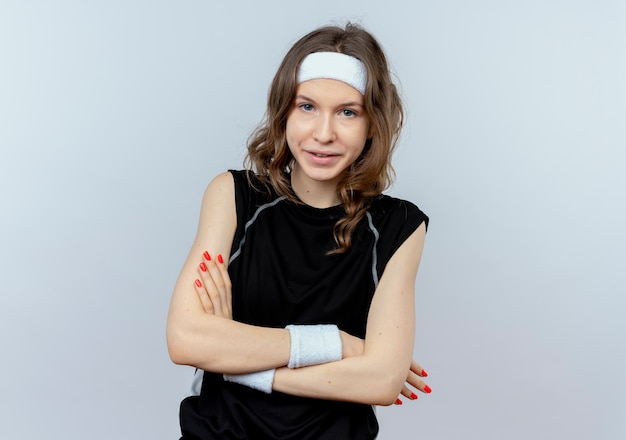 Young fitness girl in black sportswear with headband  being displeased and confused standing over white wall