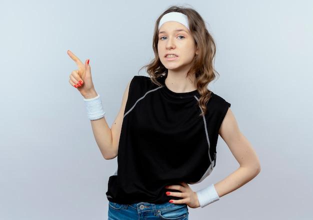 Giovane ragazza di forma fisica in abiti sportivi neri con fascia confusa puntando il dito contro qualcosa in piedi sopra il muro bianco