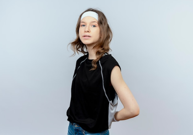 Young fitness girl in black sportswear with headband  confused standing over white wall
