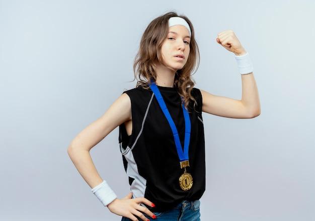 Giovane ragazza di forma fisica in abiti sportivi neri con fascia e medaglia d'oro intorno al collo alzando i pugni come un vincitore guardando fiducioso in piedi sopra il muro bianco