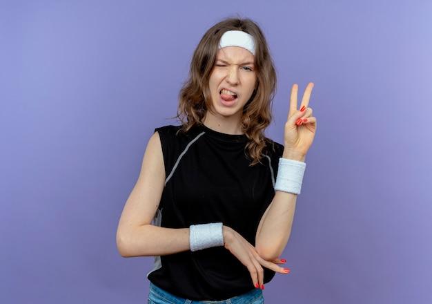 Giovane ragazza di forma fisica in abiti sportivi neri con fascia divertendosi che attacca fuori la lingua che mostra il segno di vittoria in piedi sopra la parete blu