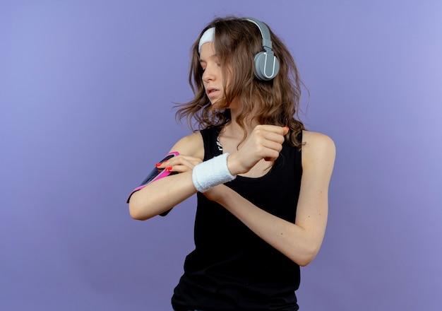 Giovane ragazza di forma fisica in abiti sportivi neri con fascia e cuffie toccando la sua mano che fissa la sua fascia da braccio dello smartphone in piedi sopra la parete blu