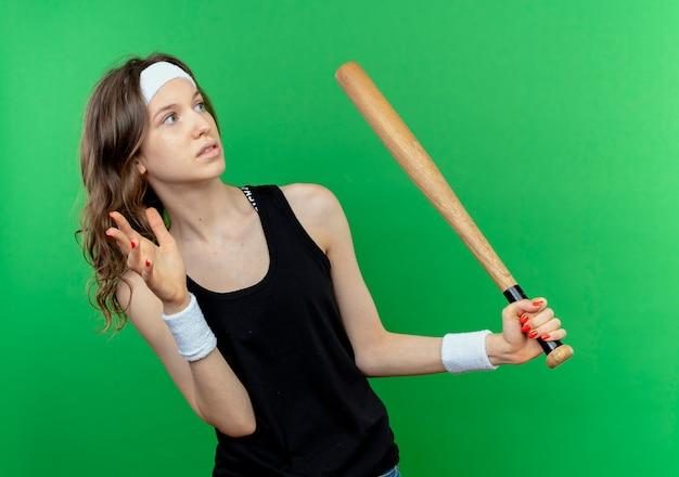 Giovane ragazza di forma fisica in abiti sportivi neri con la fascia che tiene la mazza da baseball che osserva da parte spaventata in piedi sopra la parete verde