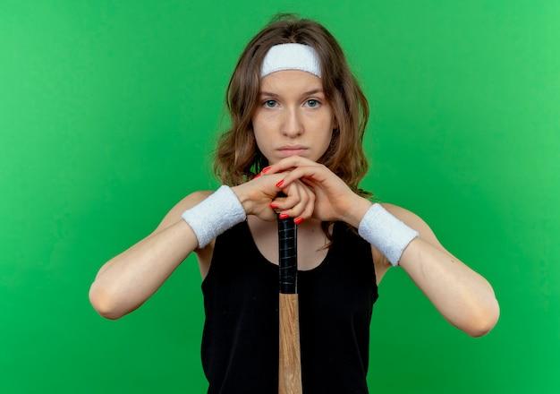 Giovane ragazza di forma fisica in abiti sportivi neri con fascia tenendo la mazza basaball con espressione fiduciosa in piedi sopra la parete verde