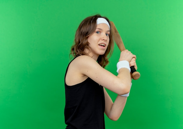 Young fitness girl in black sportswear with headband holding baseball bat  confused standing over green wall
