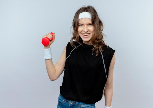 Giovane ragazza fitness in abiti sportivi neri con fascia tenendo il manubrio in mano alzata guardando fiducioso in piedi sopra il muro bianco