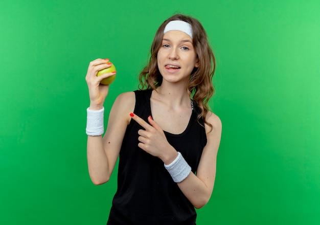 Giovane ragazza di forma fisica in abiti sportivi neri con la fascia che tiene la mela verde che indica con il dito sorridente che sta sopra la parete verde