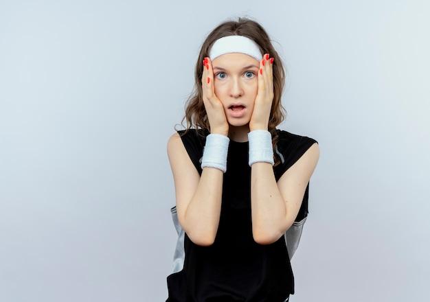 Giovane ragazza di forma fisica in abiti sportivi neri con fascia che tiene il suo viso scioccato in piedi sopra il muro bianco