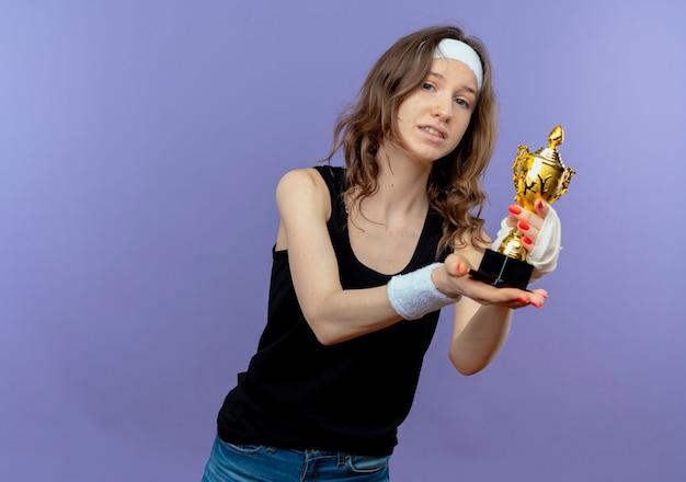 Giovane ragazza di forma fisica in abiti sportivi neri con la fascia che tiene il trofeo con la faccia di smileon timido che sta sopra la parete blu
