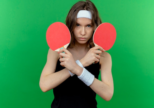 Giovane ragazza di forma fisica in abiti sportivi neri con la fascia che tiene due racchette per ping-pong scontento attraversando le mani in piedi sopra la parete verde