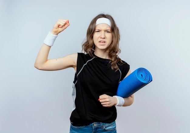Giovane ragazza di forma fisica in abiti sportivi neri con fascia che tiene materassino yoga alzando il pugno in piedi emotivo sopra il muro bianco