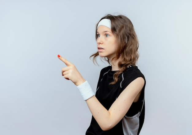 Young fitness girl in black sportswear with headband looking aside confused pointing with finger at something standing over white wall