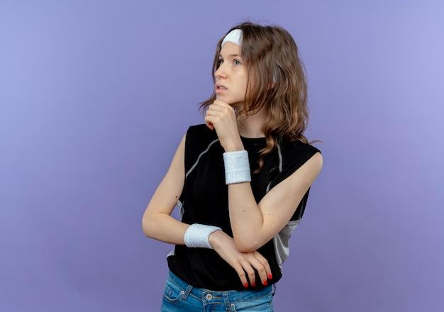 Giovane ragazza di forma fisica in abbigliamento sportivo nero con archetto che osserva da parte con la mano sul mento perplesso con espressione pensierosa sul viso in piedi sopra la parete blu