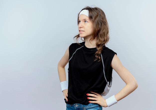 Giovane ragazza di forma fisica in abiti sportivi neri con fascia che osserva da parte con il sorriso sul viso con le braccia all'anca in piedi sopra il muro bianco
