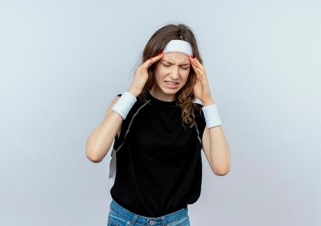 Giovane ragazza di forma fisica in abiti sportivi neri con fascia cercando di non stare bene toccando la testa che soffre di forte mal di testa in piedi sopra il muro bianco