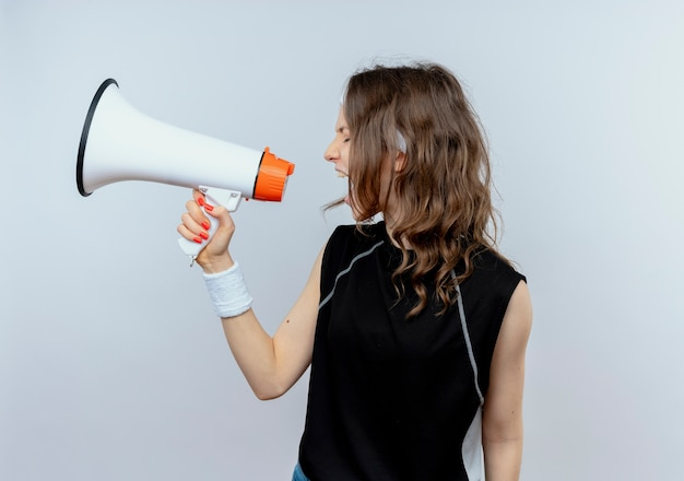 Young fitness girl in black sportswear with headband shouting to megaphone standing over white wall
