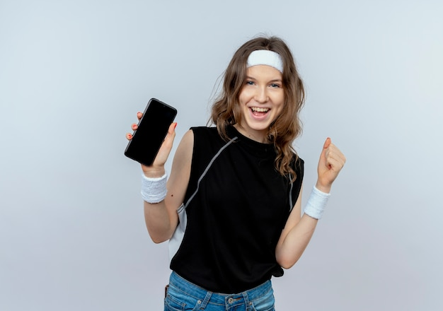 Giovane ragazza di forma fisica in abiti sportivi neri con la fascia che mostra il pugno di serraggio dello smartphone felice ed eccitato in piedi sopra il muro bianco