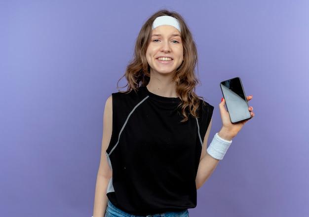 Giovane ragazza di forma fisica in abiti sportivi neri con archetto che mostra smartphone sorridente allegramente in piedi sopra la parete blu