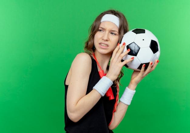Giovane ragazza di forma fisica in abiti sportivi neri con fascia e corda per saltare intorno al collo tenendo il pallone da calcio che sembra scontento in piedi sopra la parete verde