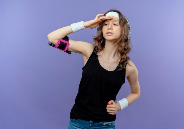 Giovane ragazza di forma fisica in abiti sportivi neri con fascia e fascia da braccio dello smartphone che guarda lontano con la mano sopra la testa in piedi sopra la parete blu
