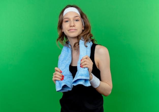 Giovane ragazza fitness in abiti sportivi neri con fascia e asciugamano intorno al collo sorridente fiducioso in piedi sopra la parete verde