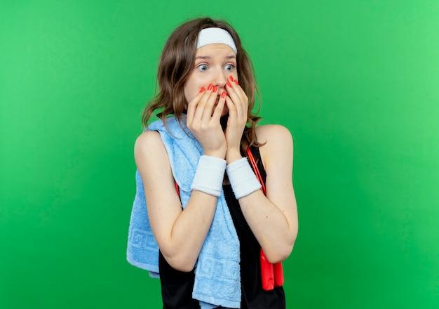 Giovane ragazza fitness in abiti sportivi neri con fascia e asciugamano sulla spalla che copre la bocca con le mani scioccate in piedi sopra la parete verde