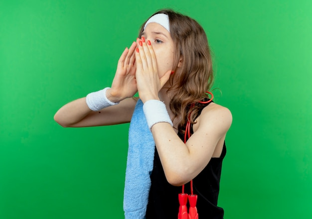Giovane ragazza di forma fisica in abiti sportivi neri con fascia e asciugamano sulla spalla che grida o chiama qualcuno con le mani vicino alla bocca in piedi sopra la parete verde
