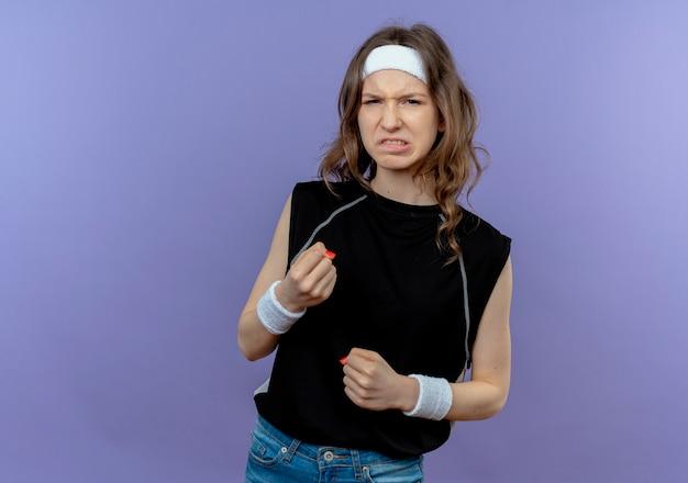 Giovane ragazza di forma fisica in abiti sportivi neri con fascia con la faccia arrabbiata che stringe i pugni in piedi sopra la parete blu