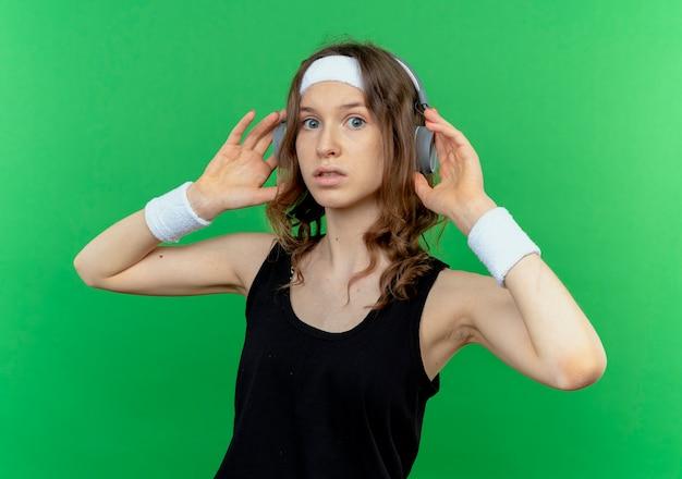 Giovane ragazza fitness in abiti sportivi neri con archetto con cuffie lookign confuso in piedi sopra la parete verde