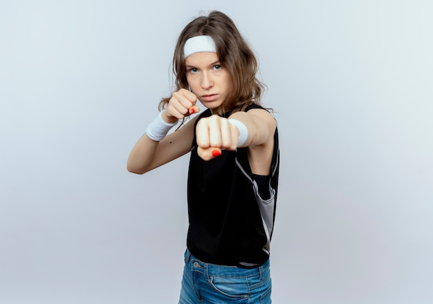 Giovane ragazza di forma fisica in abiti sportivi neri con fascia con la faccia seria in posa come un pugile con i pugni chiusi in piedi sopra il muro bianco