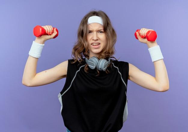 Giovane ragazza di forma fisica in abiti sportivi neri con fascia che risolve con i manubri cercando tesa sul blu