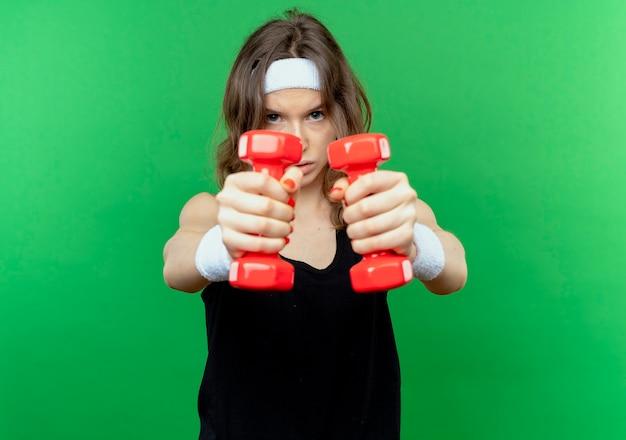 Giovane ragazza di forma fisica in abiti sportivi neri con fascia che lavora con manubri cercando in piedi teso sopra la parete verde