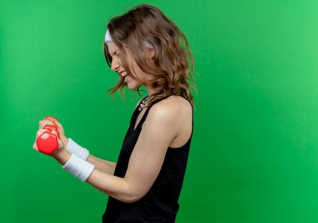 Giovane ragazza di forma fisica in abiti sportivi neri con archetto che lavora con i manubri cercando in piedi teso lateralmente sopra la parete verde