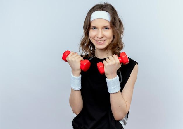 Giovane ragazza di forma fisica in abiti sportivi neri con fascia che lavora con manubri con il sorriso sul viso in piedi sul muro bianco