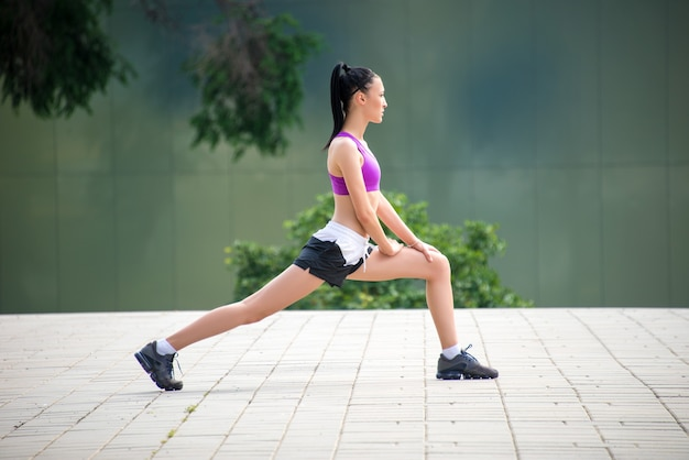 Young fitness girl doing stretching exercises outdoor