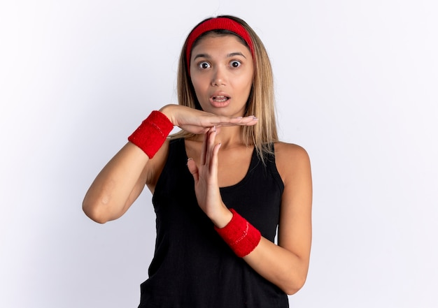 Молодая фитнес-девушка в черной спортивной одежде и красной повязке смущена, делая жест тайм-аута с руками, стоящими над белой стеной