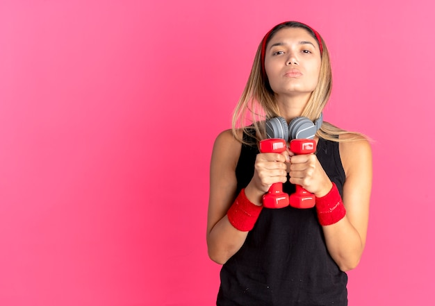 검은 색 운동복과 빨간 머리띠에 젊은 피트니스 소녀는 분홍색을 통해 자신감을 찾고 아령으로 운동을하고