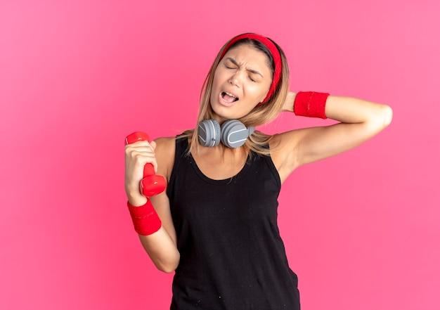 검은 운동복과 아령을 들고 빨간 머리띠에 젊은 피트니스 소녀는 분홍색을 통해 불쾌하고 좌절감을 느낍니다.